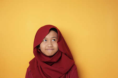 Photo pour Portrait of young Asian muslim teenage girl wearing red hijab looking up and thinking against yellow background - image libre de droit