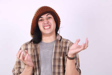 Portrait of funny young Asian man showing unhappy face, looking up with both of his palms open, shrug shoulder up, showing i don't know, rejection or denial gesture