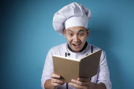 Photo for Portrait of Asian male chef reading book of recipes, finding secret recipe, against blue background - Royalty Free Image