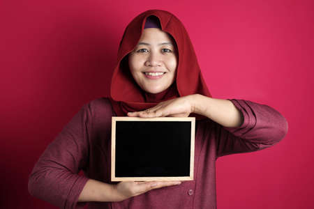 Photo pour Portrait of smart happy successful Asian muslim woman wearing hijab smiling at camera while holding and showing empty blackboard or chalk board against red background, copy space - image libre de droit