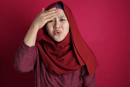Photo pour Portrait of young Asian muslim woman wearing hijab shows regret gesture, hand on her forehead, forget something important, against red background - image libre de droit