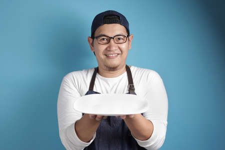 Photo pour Portrait of Asian male chef or waiter looks happy and proud presenting something on his empty white plate, copy space meal menu concept - image libre de droit