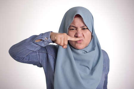 Photo pour Portrait of cute funny Asian muslim lady wearing hijab close her nose because of bad disgusting smell odor - image libre de droit