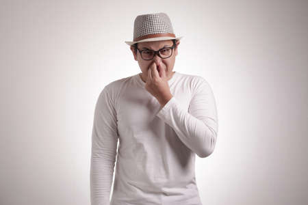 Photo pour Portrait of funny young Asian man closing his nose, smells something bad - image libre de droit