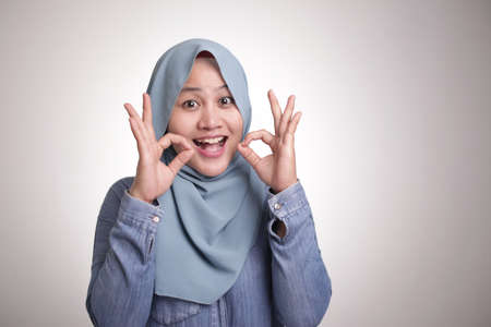 Photo pour Portrait of beautiful Asian muslim woman smiling while making delicious hand gesture with her fingers, isolated on white - image libre de droit