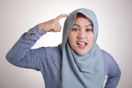 Foto de Portrait of angry Asian muslim woman pointing head as if she is asking to use your brain or do you have brain concept - Imagen libre de derechos