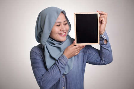 Photo pour Portrait of smart happy successful Asian muslim woman wearing hijab smiling at camera while holding and showing empty blackboard or chalk board with copy space - image libre de droit