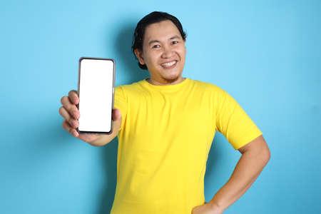 Photo pour Portrait of young young Asian man presenting smart phone mockup with selective focus - image libre de droit