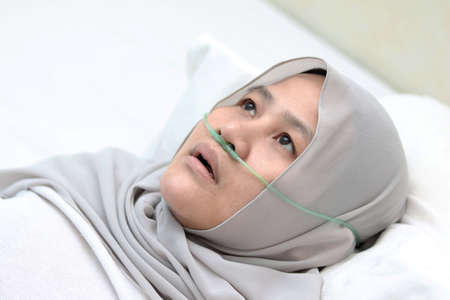 Photo pour Asian muslim female patient with nasal cannula staying in hospital room alone. Uncomfortable sick woman look pensive lying in bed. Oxygen tube on her nose, hard to breath - image libre de droit