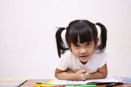 Foto de Cute adorable little Asian baby girl with pony tail hair looking at camera and smiling, happy joy excited expression when learning at home - Imagen libre de derechos