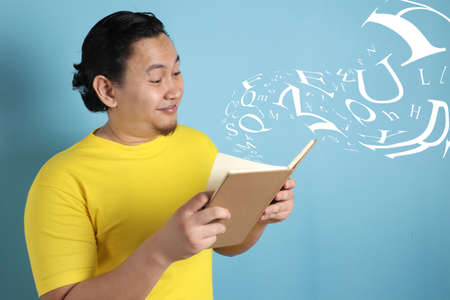 Photo for Portrait of Asian man wearing casual yellow shirt looked happy and smiling while reading a book, letters flying fro the book - Royalty Free Image