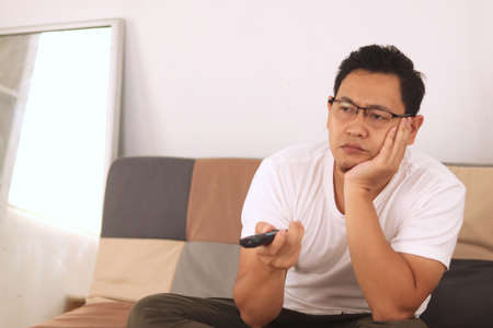 Photo pour Bored tired  young Asian man sitting on the sofa and watching TV. Trying to choose interesting TV channel with remote control - image libre de droit