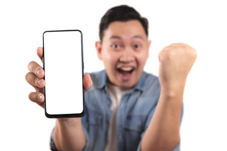 Photo pour Portrait of young young Asian man presenting smart phone mockup with happy cheerful expression, winning gesture - image libre de droit