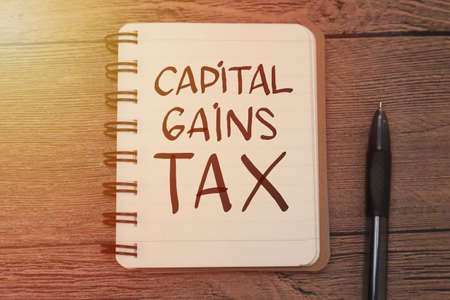 Photo pour Capital Gains Tax, text words typography written on book against wooden background, life and business motivational inspirational concept - image libre de droit