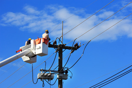 Photo for Electricians repairing wire of the power line on hydraulic platform - Royalty Free Image