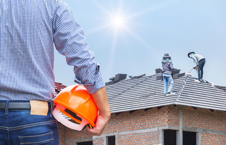 Photo pour resident engineer holding yellow safety helmet at new home building under construction site with  workers installing concrete tiles on the roof while roofing house residential development concept - image libre de droit