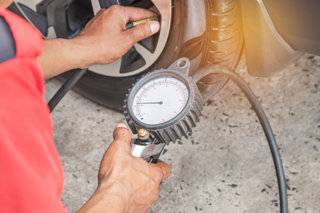 Photo pour Close up mechanic inflating put air into the tyre and checking air pressure with gauge pressure in service station - image libre de droit