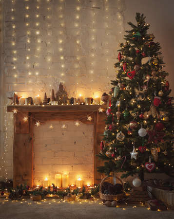 Photo pour Beautiful Christmas setting, fireplace with wooden mantelpiece fire surround, lit up decorated Christmas tree with baubles and ornaments, stars, Christmas lights, candles, selective focus - image libre de droit