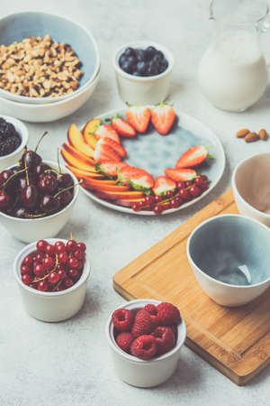 Photo for Raw vegan paleo granola or muesli made from nuts. Fruit berries platter, strawberries blueberries raspberries peach figs red currant, side view, toned, selective focus - Royalty Free Image