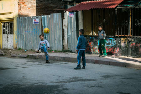 Photo for Istanbul, Turkey - January 12, 2016: Three boys are playing ball in the street of Istanbul, Turkey - Royalty Free Image