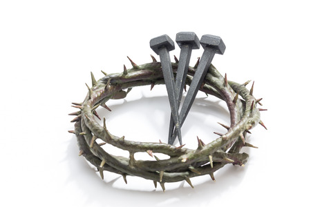 Jesus Christ crown of thorns and nails on a white background. Focus is on part of the nails.