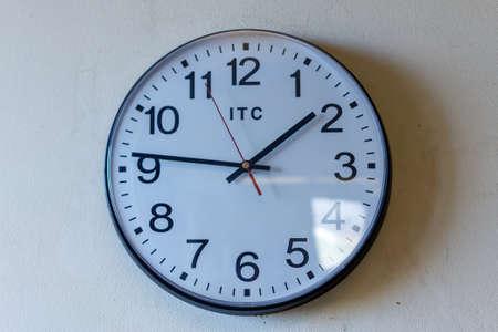 Foto de Wall clock with sun glare mounted on a white wall - Imagen libre de derechos