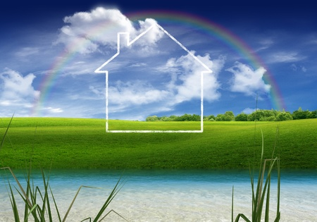 House on the river bank with rainbow in the sky in the background
