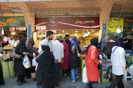 Iranian people are byiing and selling food at the bazaar, the old traditional market, along the streets in Tehran, Iran
