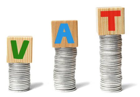 Stacks of coins and wooden blocks with letters VAT