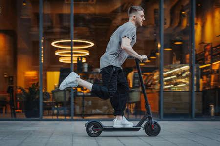 Photo pour Attractive man riding a kick scooter at cityscape background. - image libre de droit