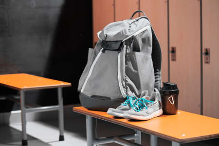 Foto de Close up of sports shoes, sport backpack and sport water bottle in gym locker room. Concept of active lifestyle, gaining muscles or loosing fat. Sport equipment. - Imagen libre de derechos