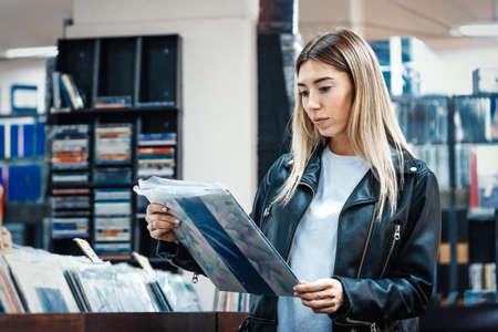 Foto de Young attractive woman choosing vinyl record in music record shop. Melomaniac or music addict concept. - Imagen libre de derechos