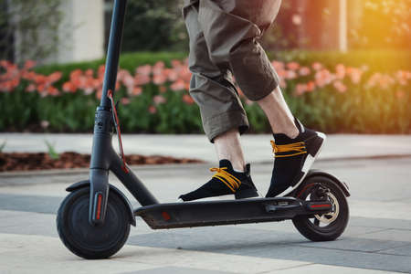 Foto de Close up of man riding black electric kick scooter at beautiful park landscape. Man is on foreground, modern building and park is on background. - Imagen libre de derechos