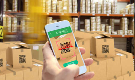 Hand holding Smart phone scanning package QR code at the warehouse, Smart logistic, Industry 4.0, Smart warehouse, Conceptual photo.