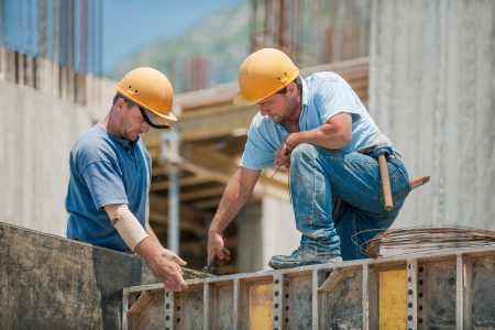 Photo for Two authentic construction workers collaborating in the installation of concrete formwork frames - Royalty Free Image