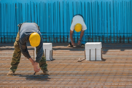 Photo for Authentic construction workers installing binding wires to reinforcement steel bars in front of a blue insulated surface prior to pouring concrete - Royalty Free Image