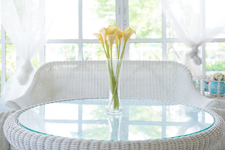 Yellow flower in vase on table and window sill background  Vintage style decorate