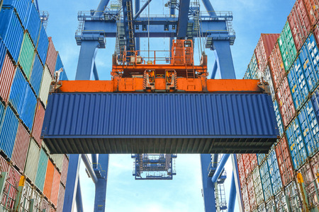 Photo pour Shore crane loading containers in freight ship - image libre de droit