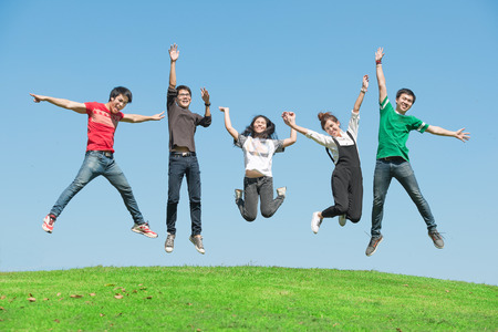 summer, holidays, vacation, happy people concept - group of friends jumping on the park