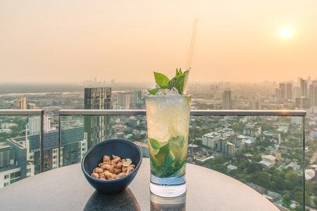 Photo for Mojito cocktail and cashews on table in rooftop bar - Royalty Free Image
