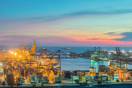 Foto de Container Cargo freight ship with working crane bridge in shipyard at dusk for Logistic Import Export  - Imagen libre de derechos