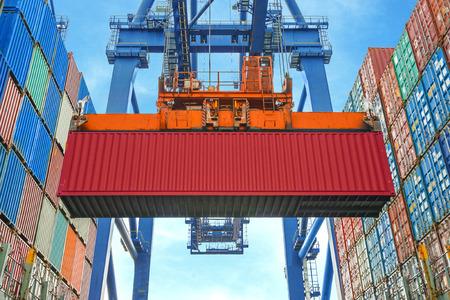 Photo pour Shore crane loading containers in freight ship - image libre de droit