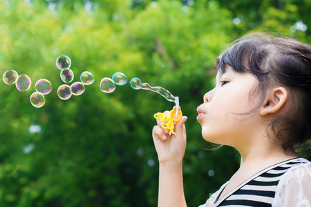 Asian little girl blowing soap bubbles in green park