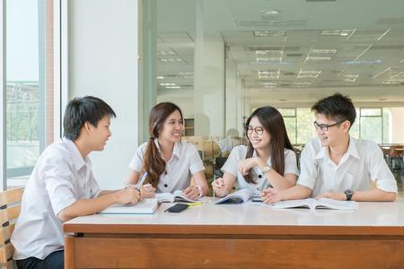 Foto de Group of asian students in uniform studying together at classroom - Imagen libre de derechos