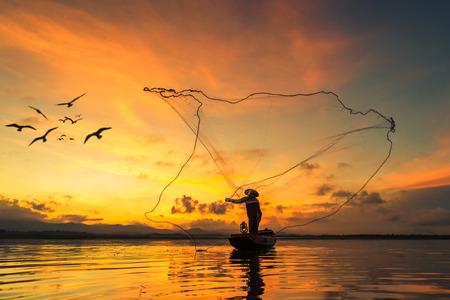 Foto de Fisherman fishing at lake in Morning, Thailand. - Imagen libre de derechos