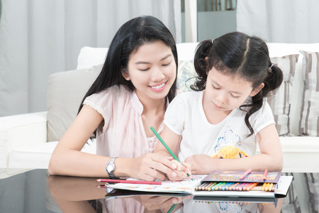 family, children and happy people concept - mother and daughter drawing at home