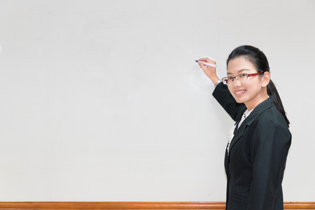 Asian woman writing something in whiteboard with pen and explaining