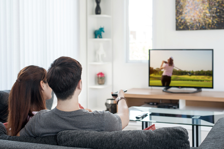 Young Asian couple waching golf sport on tv at home