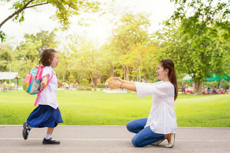 Photo pour Family, Kids and Mother - Kids student running into mother's hands to hug her. Family having fun in the park. Kids is happy to meet her mother - image libre de droit