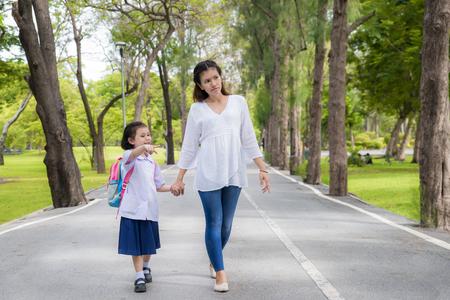 Foto de Asian mother and daughter student walking to school.Pupil student. - Imagen libre de derechos
